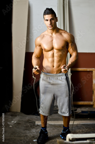Athletic, muscular young man shirtless with jumping rope