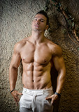 Attractive muscleman against rough wall