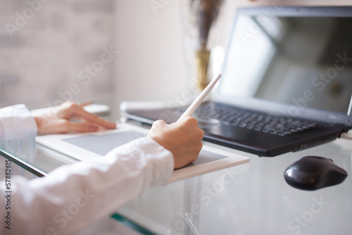 Woman designer using a graphics pad with notebook