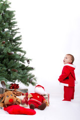 Fascinated Santa Baby boy standing next to Christmas tree.