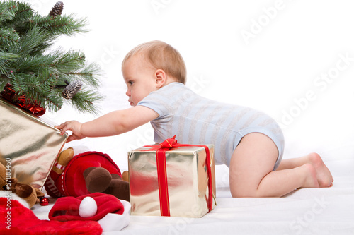 Baby boy reaching for Christmas gifts.