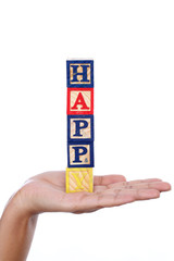 "Word ""Happy"" of wooden blocks in woman hand"