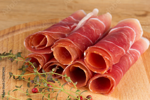 slices of jamon on a wooden table with fresh herbs