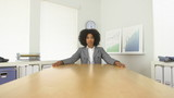 African American business woman sitting at end of conference tab