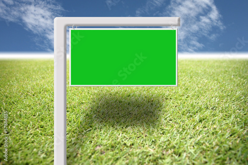 Green sign on the lawn and blue sky.