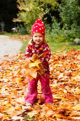 Kleines Mädchen mit Ahornblättern