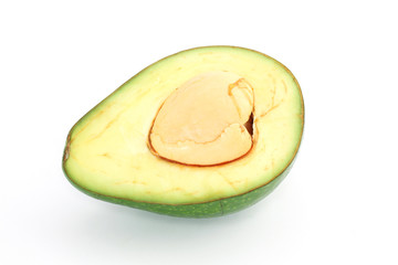 Avocado cut in half with the pit on white