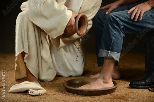 Leinwanddruck Bild Jesus Washing Feet of Man in Jeans