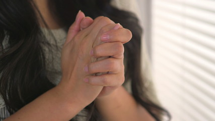 Troubled Japanese woman clasping her hands