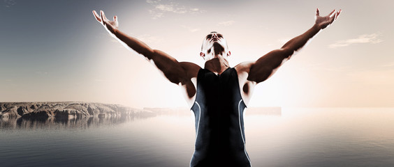 Muscled fitness triathlon athlete. Arms spread wide. Victory. St