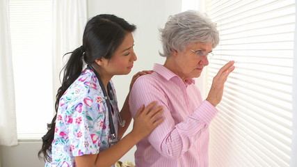 Mature Caucasian woman being consoled by Japanese nurse