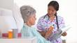 Japanese nurse explaining medication to mature patient