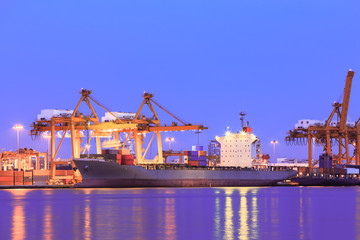 Container cargo freight ship at port twilight