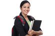 Happy young female student with books and backpack