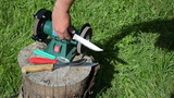 Hand grinder knives with electric tool on outdoor log