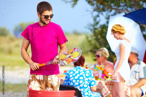 happy man prepares food on the grill, family picnic