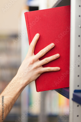Student taking a book from a bookshelf