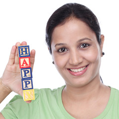 "Young woman holding wooden blocks of word ""Happy"""