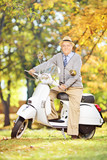 Cheerful senior man on a scooter posing in a park
