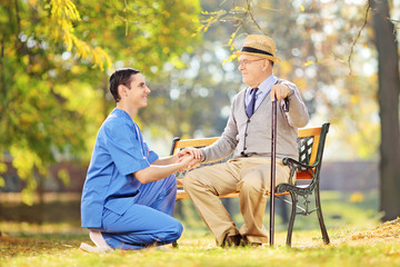 Healthcare professional helping senior man sitting on a bench