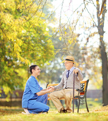Healthcare professional helping senior man sitting outside