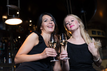 Two female friends toasting in a nightclub