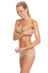 Smiling young woman in lingerie applying creme on arm