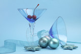 Festive Christmas martini cocktail glasses on blue background.