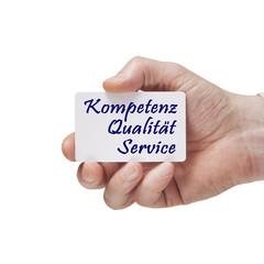 Hand mit Notiz Kompetenz, Qualität, Service.