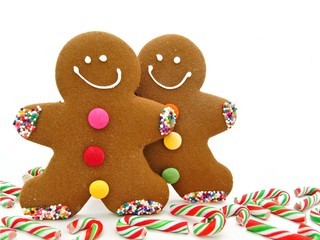 Two Gingerbread Men among scattered candy canes
