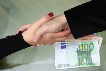 businessmen and businesswoman handshake with  money on desk
