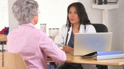 Japanese doctor prescribing medication to mature woman patient