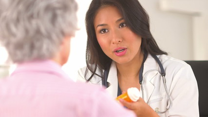 Asian doctor prescribing medication to mature woman patient