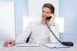 Businessman Sitting In Front Of Computer Talking On Telephone