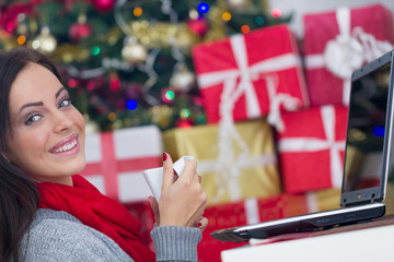woman using laptop on Christmas night and drink coffee