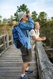 Senior Couple Hiking and Birdwatching on Old Wooden Foot Bridge poster