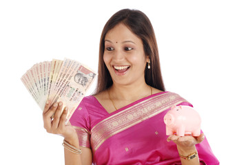 Happy young woman holding piggy bank and Indian currency