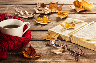 Hot coffee, book, glasses and autumn leaves on wood