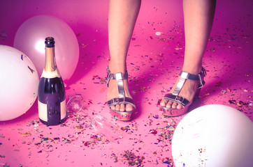 Woman's feet with confetti on the floor and champagne