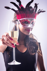 Woman wearing red mask at masquerade party drinking champagne