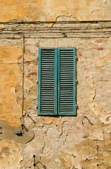 Grüner Klappladen geschlossen an gelber Wand