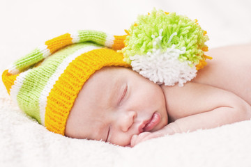sleeping newborn baby with bright hat