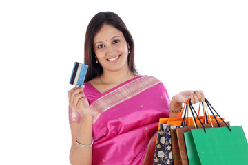 Smiling Indian woman with shopping bags and credit card