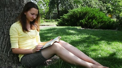 Teen girl reads the Bible sitting in the park