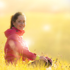 Pretty woman relaxing on a meadow during sunrise