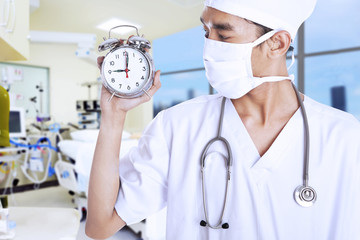 A male doctor holding an alarm clock