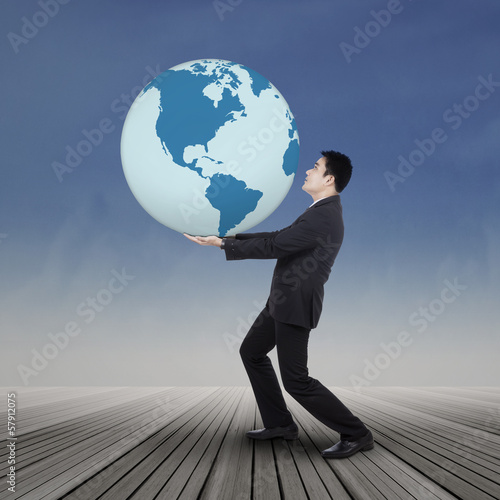 Asian businessman carrying the earth
