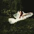 Adorable young caucasian bride in garden.
