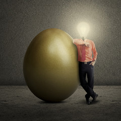 Bulb head businessman standing with golden egg