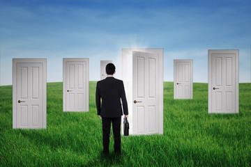 Businessman walking into opportunity doors